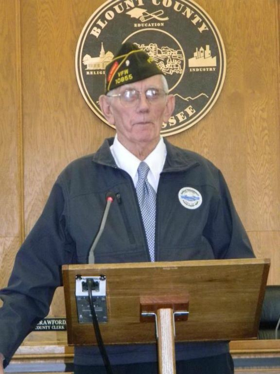 Man in blue jacket and white shirt, with glasses and hat, stands speaking at podium